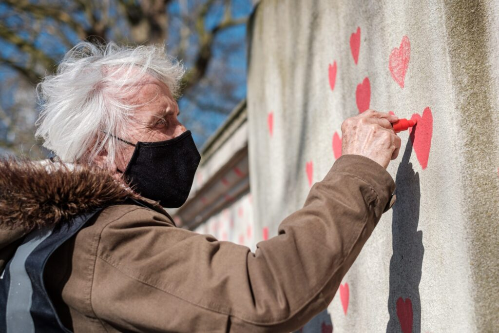 Elderly woman painting hearts on street wall - Featured image
